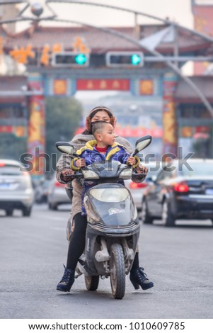 HENGDIAN-CHINA-DEC. 29, 2014. Mother with child on electric scooter. China has 200 million e-bikes running on the road, a tenfold increase from 2005. They are manufactured by 700 Chinese companies.