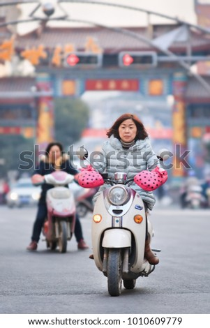 HENGDIAN-CHINA-DEC. 29, 2014. Woman on retro design electric scooter. China has 200 million e-bikes running on the road, a tenfold increase from 2005. They are manufactured by 700 Chinese companies.