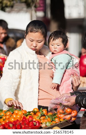 HENGDIAN-DEC. 29, 2015. Young Chinese mother with her child. The Chinese Communist Party announced in 2013 to relax the one-child policy. Families can have two children if one parent is an only child. - stock photo