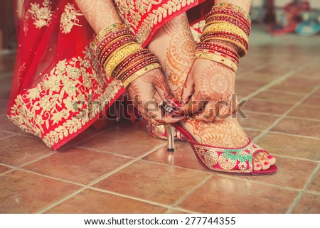 Henna mehndi wedding design on the feet and hands of red dressed up bride  - stock photo