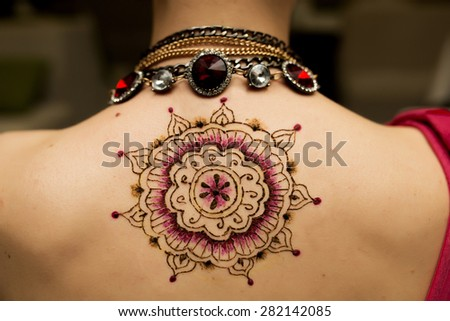 Hennaed beautiful female back, round mandala image, traditional Indian, Pakistani, African, Oriental motifs, cultural traditions and customs. Mehendi made of brown, black red henna paste. Professional - stock photo