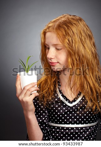 Her Future: Young girl looking thoughtful while holding a small plant. Metaphor for sustainability or environmental issues. - stock photo