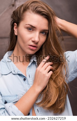 Her glance is knocking down. Beautiful young woman in shirt holding hand in hair and looking at camera while standing against metal background - stock photo