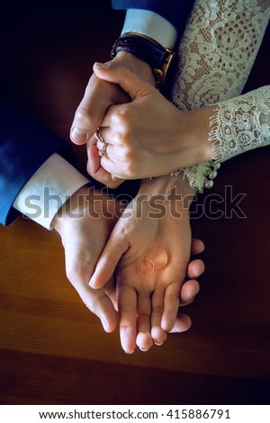 her hand in his hand, near a bouquet. love concept. jewelry, men and women. manicure. wedding rings in shes hands. - stock photo