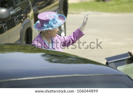 Her Majesty Queen Elizabeth II in bright purple outfit and hat, waving to the crowd as she enters Presidential Limousine in Williamsburg Virginia, May 4, 2007 - stock photo