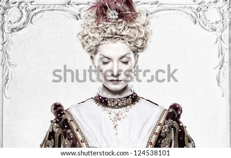 Her royal highness standing against wall with stucco works - stock photo