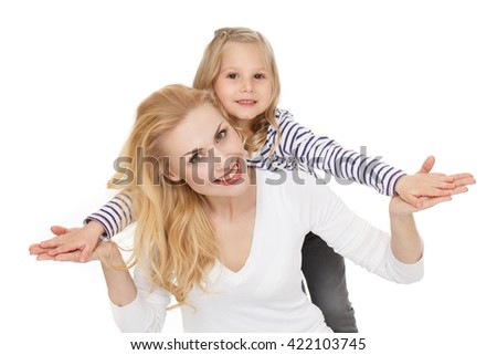 Her sense of life. Portrait of a charming adult female posing with her little daughter standing behind on white background. - stock photo