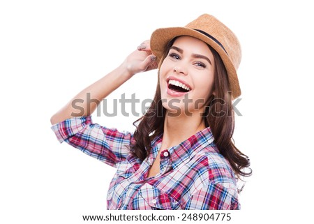 Her smile is knocking down. Beautiful young woman in funky wear adjusting hat and smiling at camera while standing against white background - stock photo
