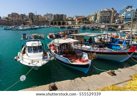 HERAKLION, GREECE - JULY 16, 2016: Crete. Moored fishing boats in the seaport. In the background the city's neighborhoods.