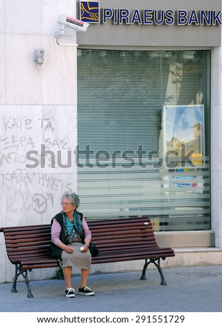 HERAKLION, GREECE - MAY 01, 2010: Aged woman sits on the bench next to the closed bank - stock photo