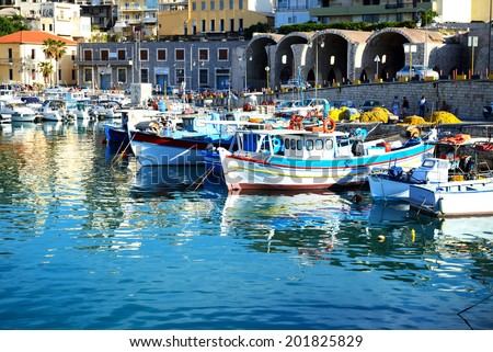 HERAKLION, GREECE - MAY 12: The traditional Greek fishing boat are near pier and tourists on May 12, 2014 in Heraklion, Greece. Up to 16 mln tourists is expected to visit Greece in year 2014.