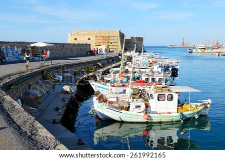 HERAKLION, GREECE - MAY 12: The traditional Greek fishing boat are near pier and tourists on May 12, 2014 in Heraklion, Greece. Up to 16 mln tourists is expected to visit Greece in year 2014. - stock photo