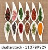 Herb and spice selection in white porcelain dishes over hessian background. - stock photo