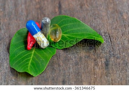 Herb capsule on leaves on wooden background - stock photo
