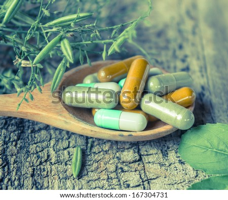Herb capsule on wooden spoon on wooden background.  - stock photo