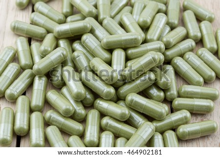 Herb capsule on wooden table, wood background.