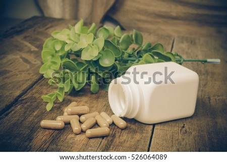 Herb capsule spilling out of a white  bottle on wood .
