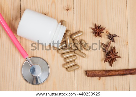 herb capsules and stethoscope on wood table - stock photo