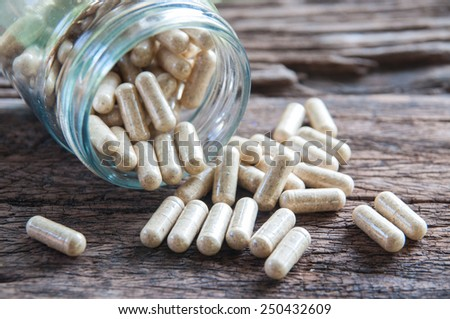 Herb capsules on wooden background - stock photo