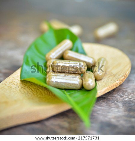 Herb capsules on wooden ladle  - stock photo