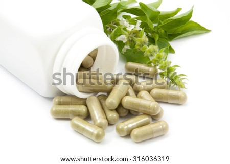 herb capsules spilling out of a bottle  isolated on white - stock photo
