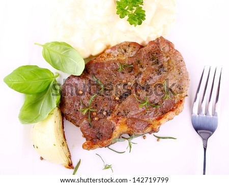 Herb Grilled steak meat with onion, basil and potato salad, top view - stock photo