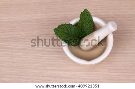 herb in a mortar on  wood table black background. - stock photo