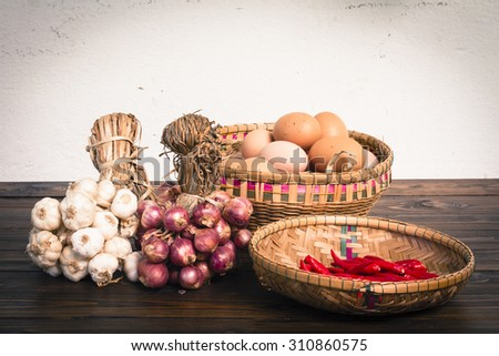 Herb ingredients,  onion, garlic and eggs on dark wood table with speckled background, retro style - stock photo