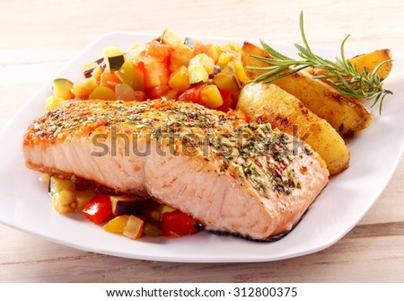 Herb Roasted Fillet of Salmon Served on White Plate with Roasted Potato Wedges and Fresh Chopped Salsa Garnished with Herbs - stock photo