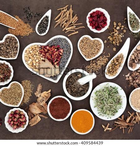 Herb selection used in female alternative herbal medicine over lokta paper background. - stock photo