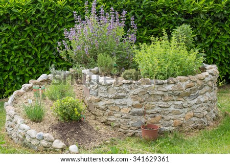 Herb spiral stone with kitchen herbs - stock photo