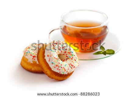 Herb tea cup with mint and two colorful dough nuts. Isolated background. - stock photo