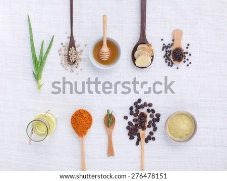 herb variety on rustic white background from top view, oil, coffee, beans, pepper, aloe vera, turmeric, ginger, rosemary - stock photo