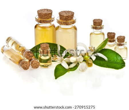 Herbal aromatherapy essential oil in bottles with fresh citrus flowers isolated on white  - stock photo