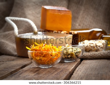 herbal calendula in the glass bowl, on wooden background - stock photo