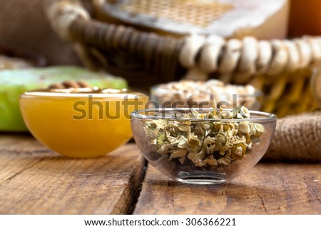 herbal camomile in the glass bowl, on wooden background - stock photo