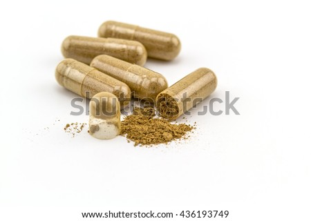 Herbal capsule and powder on white background. - stock photo