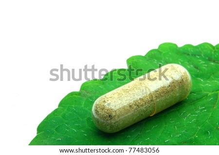 Herbal capsule on melisa leaf - stock photo