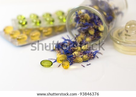 herbal capsules and dried herbs cornflower on white - stock photo