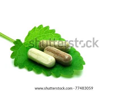 Herbal capsules on melisa leaf - stock photo