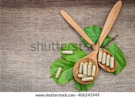 Herbal capsules on wooden spoon. herb for healthy living.  - stock photo