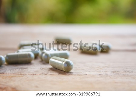 Herbal capsules on wooden table - stock photo