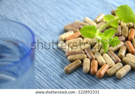 herbal capsules with mint leaves and glass of water - stock photo