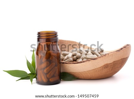 Herbal drug capsules in brown glass bottle isolated on white background cutout. Alternative medicine concept. - stock photo
