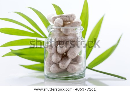 Herbal drug capsules in glass bottle with green l Alternative medicine concept. - stock photo