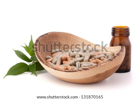 Herbal drug capsules in wooden plate isolated on white background cutout. Alternative medicine concept. - stock photo