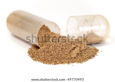 Herbal drug shown spilling out of open capsule. - stock photo