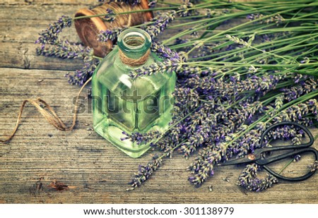 Herbal lavender oil with fresh flowers bouquet on wooden background. Country style still life. Vintage toned picture with vignette - stock photo