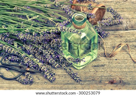 Herbal lavender oil with fresh flowers on wooden background. Vintage style toned photo - stock photo