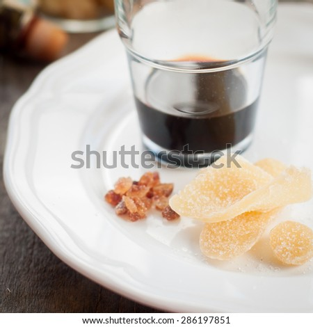 Herbal Liqueur with Crystallized Ginger and Brown Rock Sugar on a White Plate, shallow dof, square - stock photo